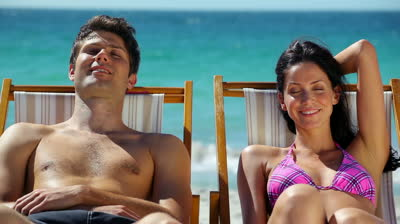 stock-footage-couple-resting-on-deck-chairs-on-the-beach